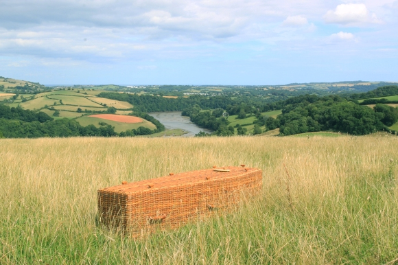 Golden Wicker Traditional Coffin overlooking river